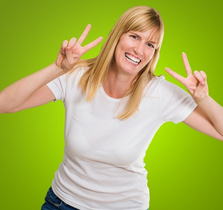 Happy Woman Showing Peace Sign against a green background Stock Photo - 16290920