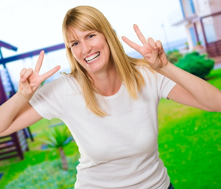 Happy Woman Showing Peace Sign at a playground, outdoor Stock Photo - 16291027