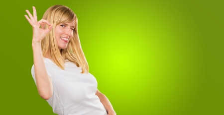 Happy Woman Showing Ok Sign against a green background Stock Photo - 16289447
