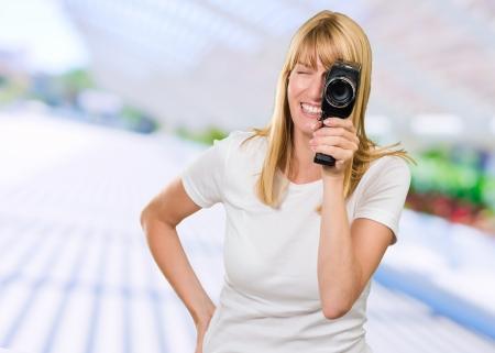 amateur: Mujer feliz que mira a través de cámara al aire libre en la calle Foto de archivo