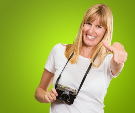 Happy Woman With Old Camera Showing Thumb Up against a green background photo