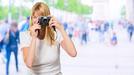 snap: Woman Looking Through Old Camera at a street full of people