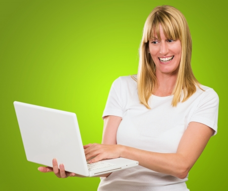 Happy Woman Looking At Laptop against a green background Stock Photo - 16289179