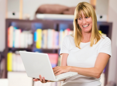 Happy Woman Looking At Laptop at a library Stock Photo - 16290081