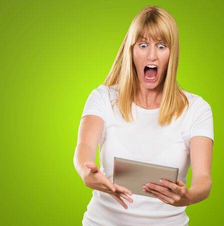 opened: Shocked Woman Looking At Digital Tablet against a green background