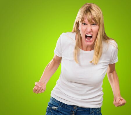 aggressive people: Portrait Of Angry Woman against a green background