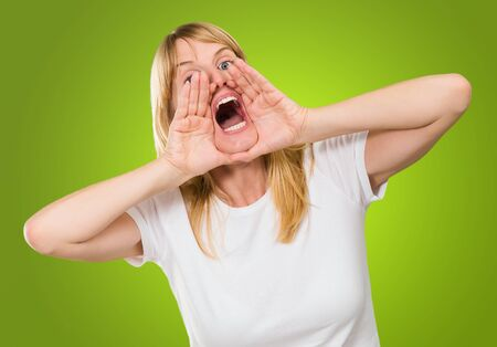 woman shouting: Portrait of a woman shouting against a green background