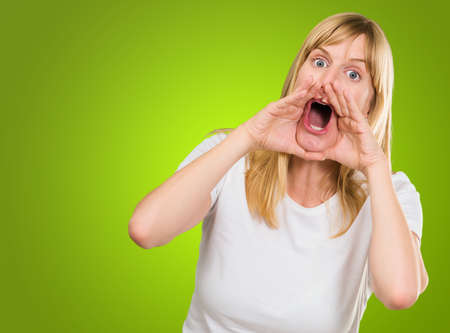 Portrait of a crazy woman shouting against a green background Stock Photo - 16288843