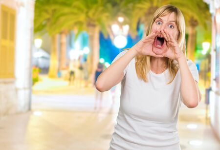 Portrait of a crazy woman shouting at a city by night, outdoor photo