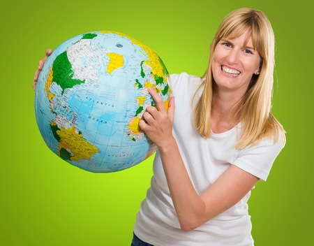 Portrait Of Woman Holding Globe against a green background Stock Photo - 16289453
