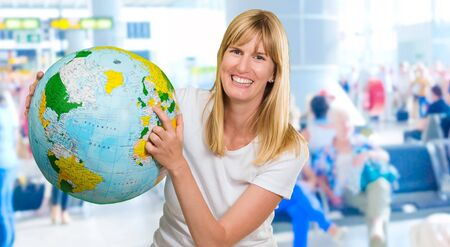 Portrait Of Woman Holding Globe at the airport waiting area photo