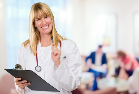 waiting area: happy female doctor holding a clipboard in a waiting area