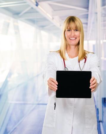 passageway: Happy Doctor Showing Digital Tabletin a passageway, indoor Stock Photo