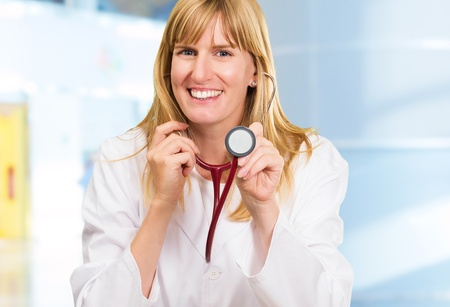 listening device: Happy Doctor Holding Stethoscope against an abstract background, indoor