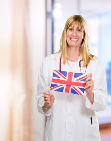 Happy Doctor Holding British Flag in an office photo