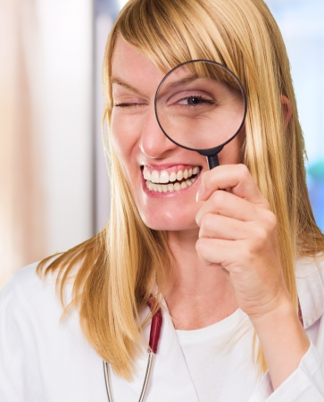 Happy Doctor Looking Through Magnifying Glass against an abstract background photo