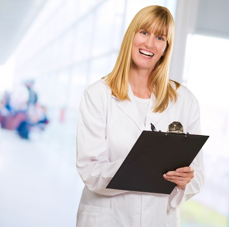 Portrait Of Happy Doctor Writing On Clipboard against an abstract background photo