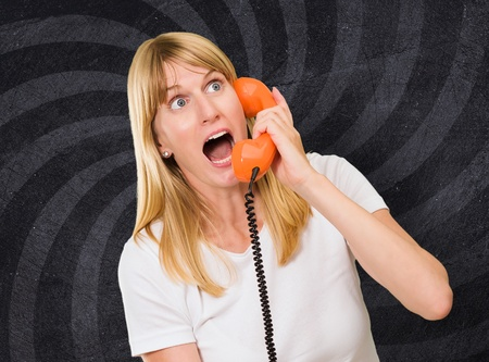 shocked woman talking on telephone against a spiral vintage background Stock Photo - 16291085