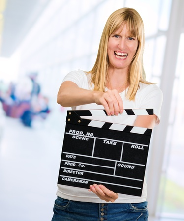 Happy Woman Holding Clapper Board, indoor photo