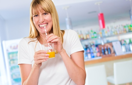Woman Drinking Juice in a bar, indoor photo