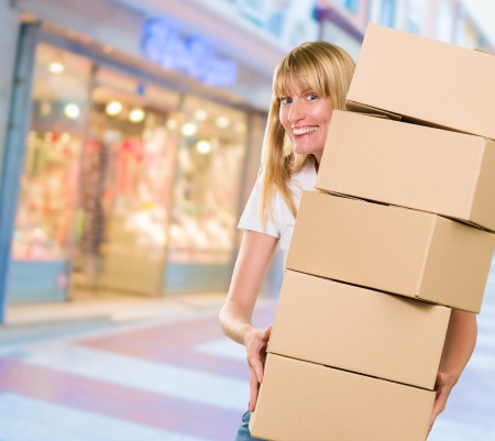 moving office: woman holding a pile of boxes at the street Stock Photo