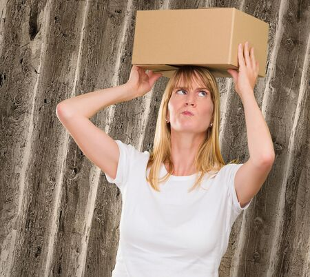 woman holding a box on her head against a grunge background photo