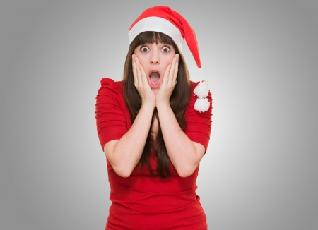 scared woman wearing a christmas hat against a grey background Фото со стока - 16290983