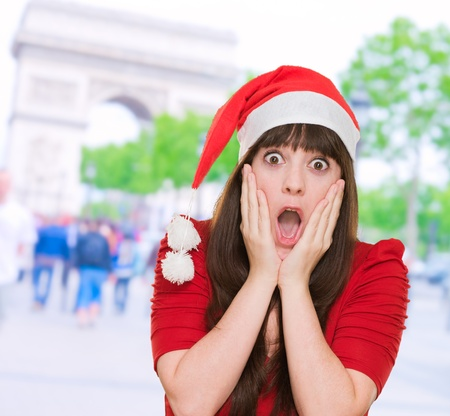 scared woman wearing a christmas hat against a street background photo