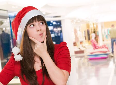 woman thinking and wearing a christmas hat at a mall, indoor Stock Photo - 16290917