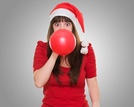 woman blowing balloon and wearing a christmas hat against a grey background photo