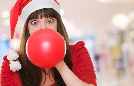 woman blowing balloon and wearing a christmas hat at the mall, indoor photo