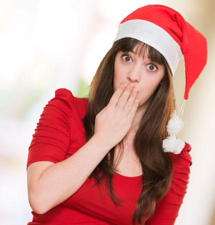 woman wearing a christmas hat and covering her mouth against an abstract background Stock Photo - 16290682