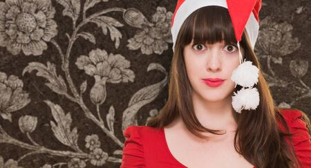confused woman wearing a christmas hat against a vintage background photo