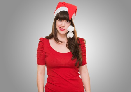funny woman wearing a christmas hat against a grey background photo
