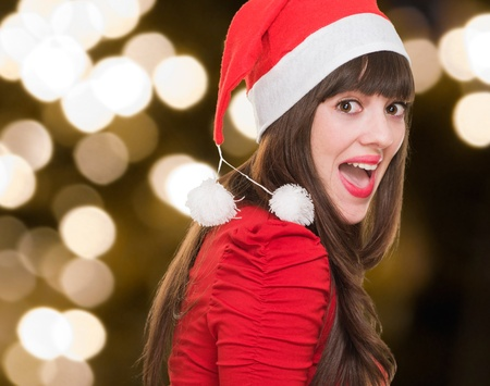 happy woman wearing a christmas hat against gold lights Stock Photo - 16290342