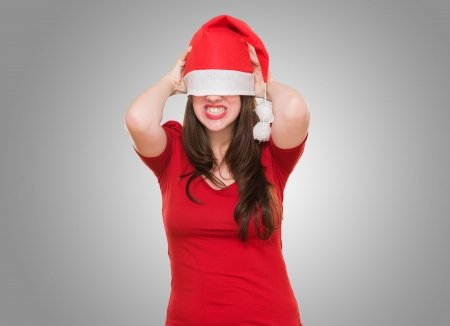 angry woman with a christmas hat covering her eyes against a grey background photo