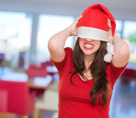angry woman with a christmas hat covering her eyes, indoor photo