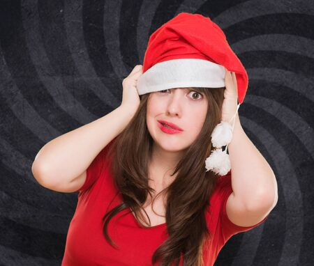 worried woman wearing a christmas hat against a vintage background photo