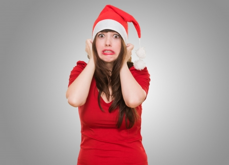 scared woman wearing a christmas hat against a grey background