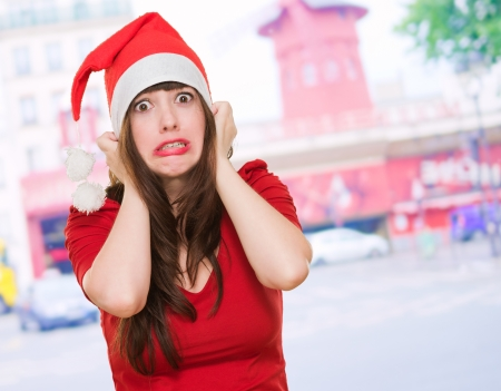 holiday stress: scared woman wearing a christmas hat, outdoor