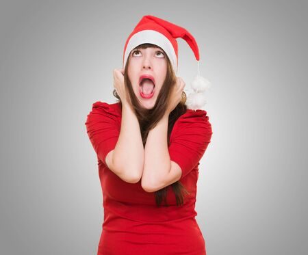 stressed woman wearing a christmas hat against a grey background photo