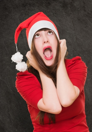 stressed woman wearing a christmas hat against a grunge background photo