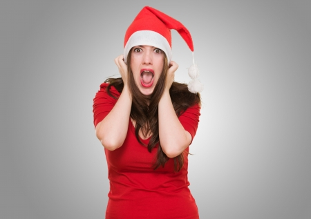 horrified: furious woman wearing a christmas hat against a grey background