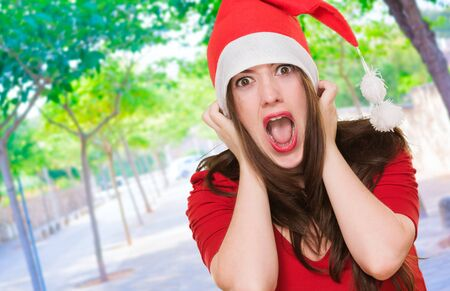 furious woman wearing a christmas hat, outdoor photo