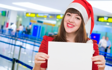 happy christmas woman holding a blank card at the airport photo
