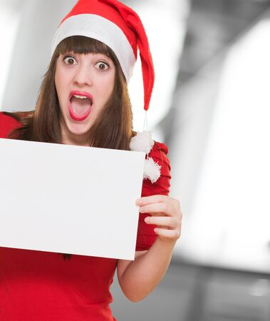surprised christmas woman holding a blank card against an abstract background Stock Photo - 16290637