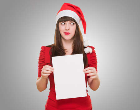 worried christmas woman holding a blank card against a grey background photo