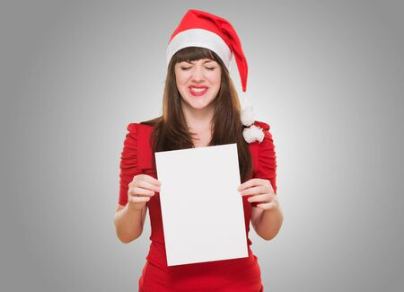 upset christmas woman holding a blank card against a grey background photo