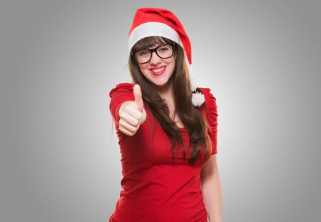 christmas woman doing a thumbs up gesture against a grey background Stock Photo - 16290921