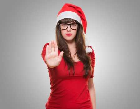 belay: christmas woman doing a stop gesture against a grey background